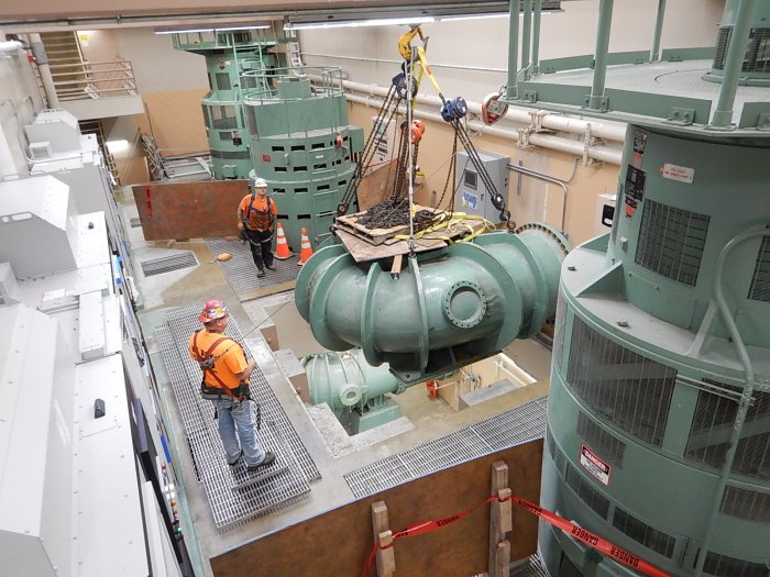 Crews lower a large pump into place at a treatment plant.
