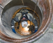 Employees inspect pipes through a maintenace hole