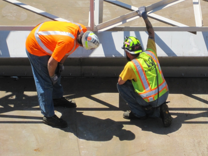 Workers inspect the alignment of the new ducts.