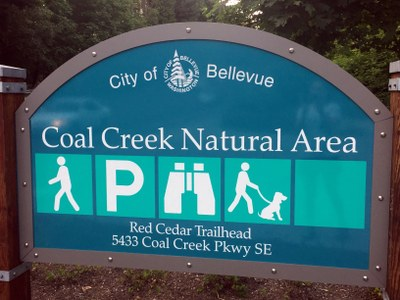 This image shows a blue decorative sign that has a City of Bellevue log on top and location: Coal Creek Natural Area. There are activity icons for hiking, parking, viewing, and dog walking. The address reads: Red Cedar Trailhead, 5433 Coal Creek Parkway SE.