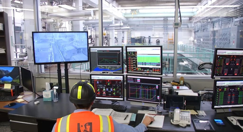 A wastewater operator sits facing away from us, in front of multiple computer screens that help monitor the treatment plant processes