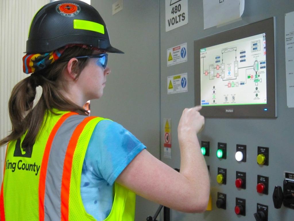 A female wastewater operator wearing a hardhat, googles and safety vest checks a screen and control panel in the treatment plant