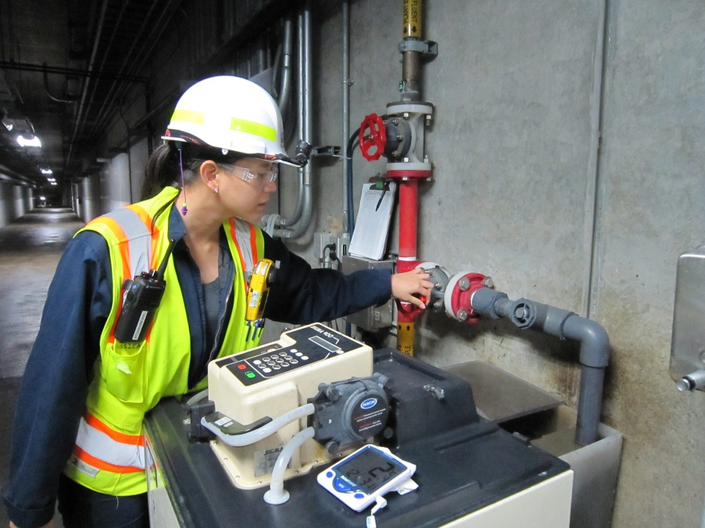 A female wastewater worker wearing a hardhat, googles and safety vest checks a wastewater treatment plant process and equipment