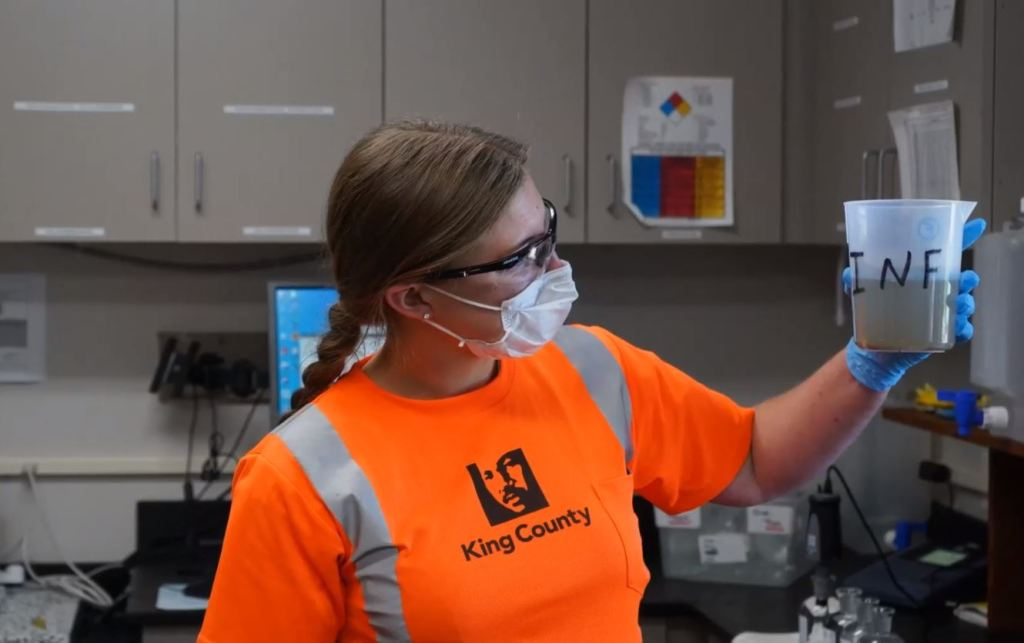 A female wastewater operator wearing a mask, googles and safety shirtholds up a container of water that is part of testing the treatment plant process